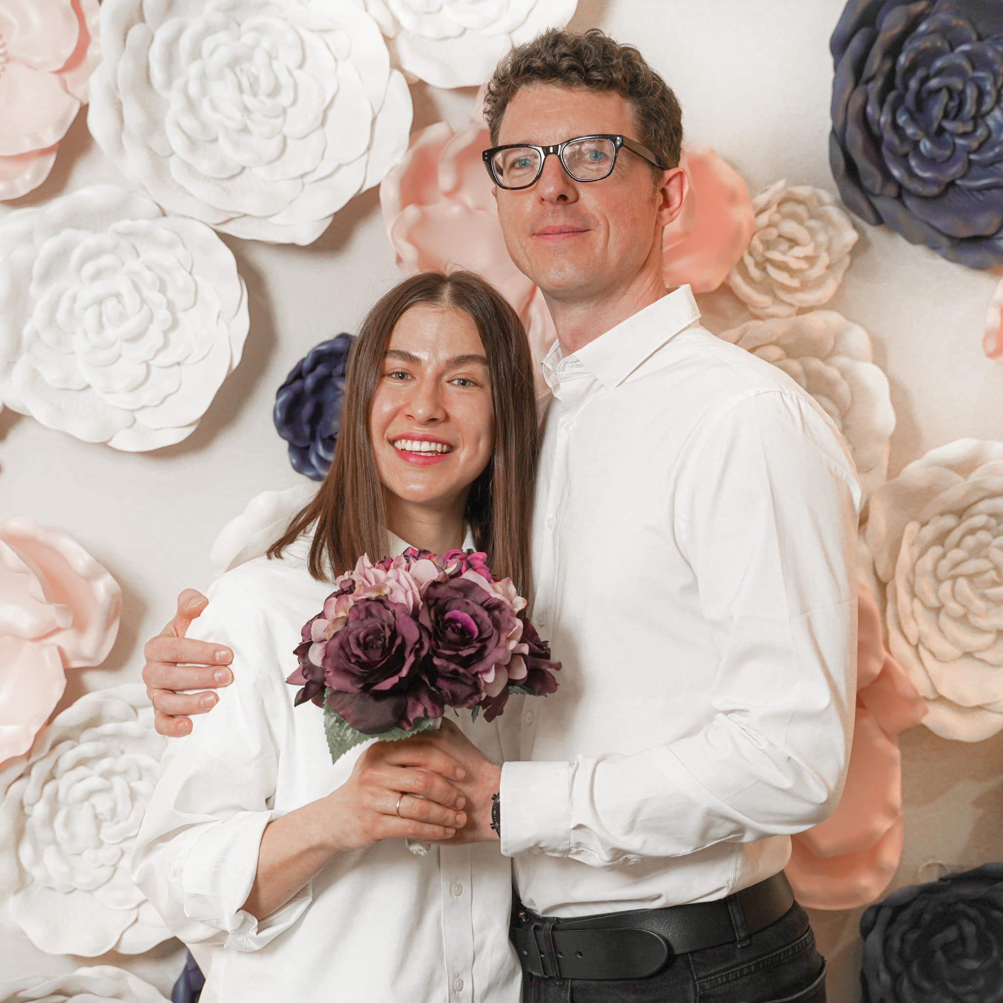 Couple at Wedding against flower wall