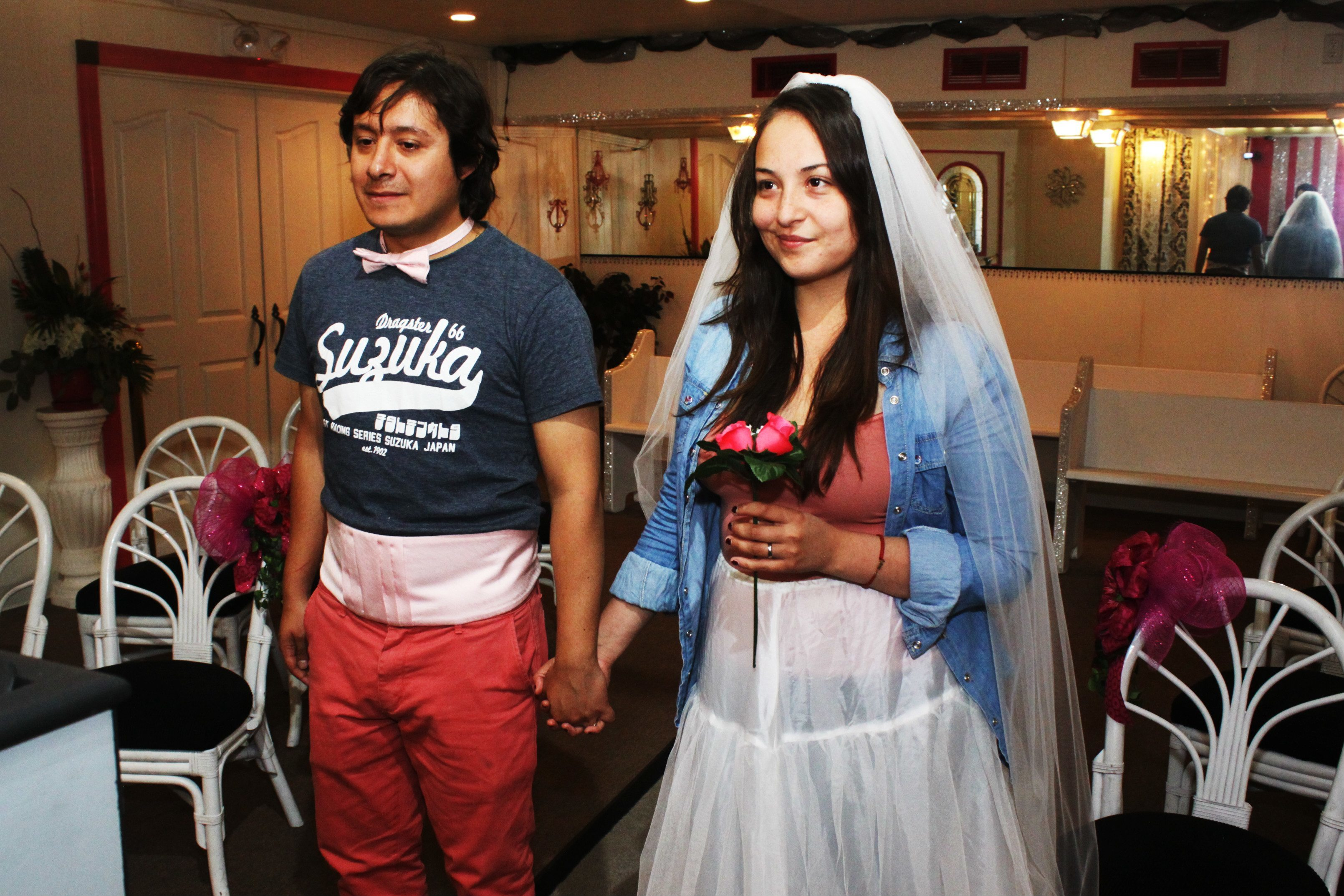 Bride and groom stands inside of chapel, bride holds bouquet
