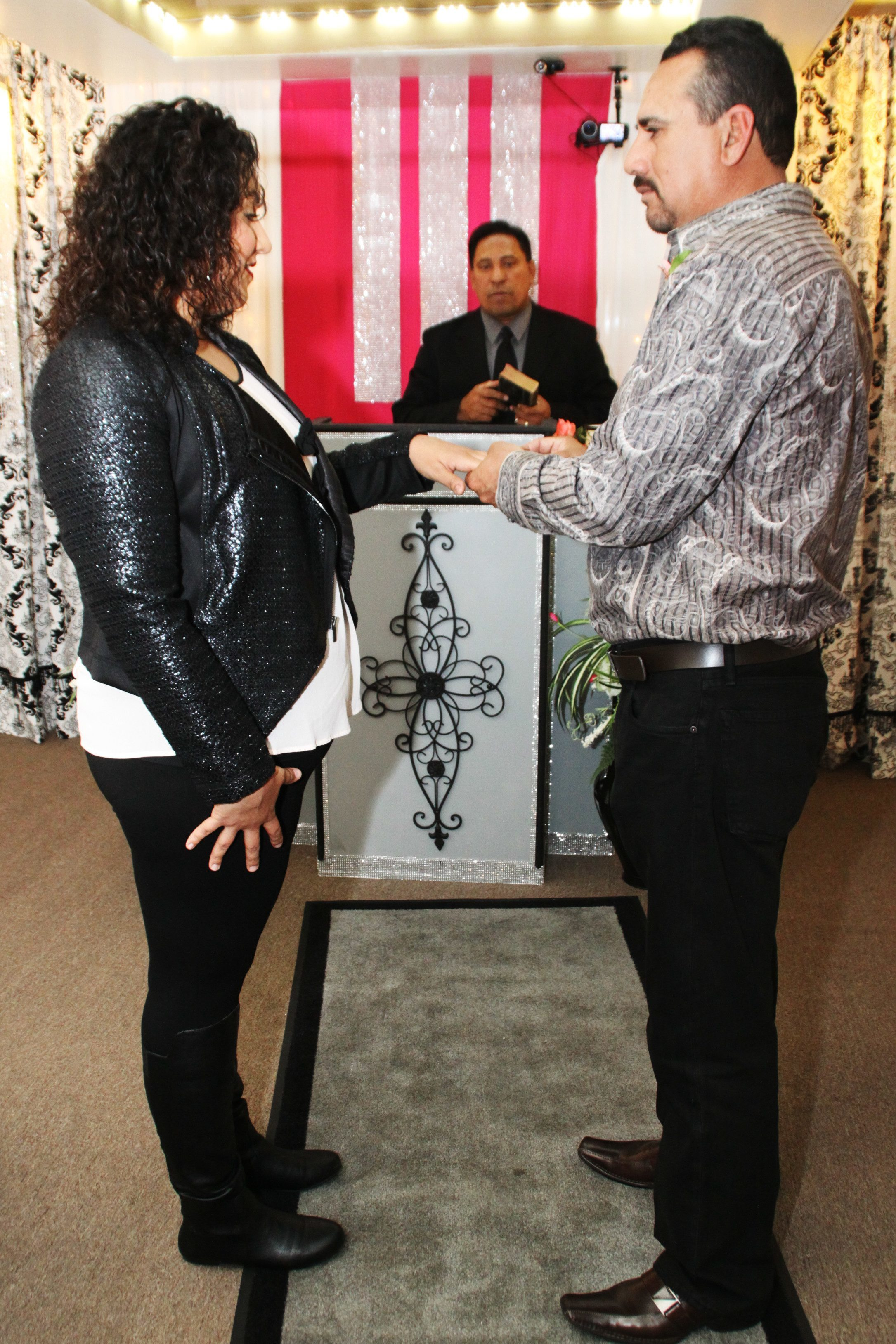 Ring exchange between bride and groom, minister in background