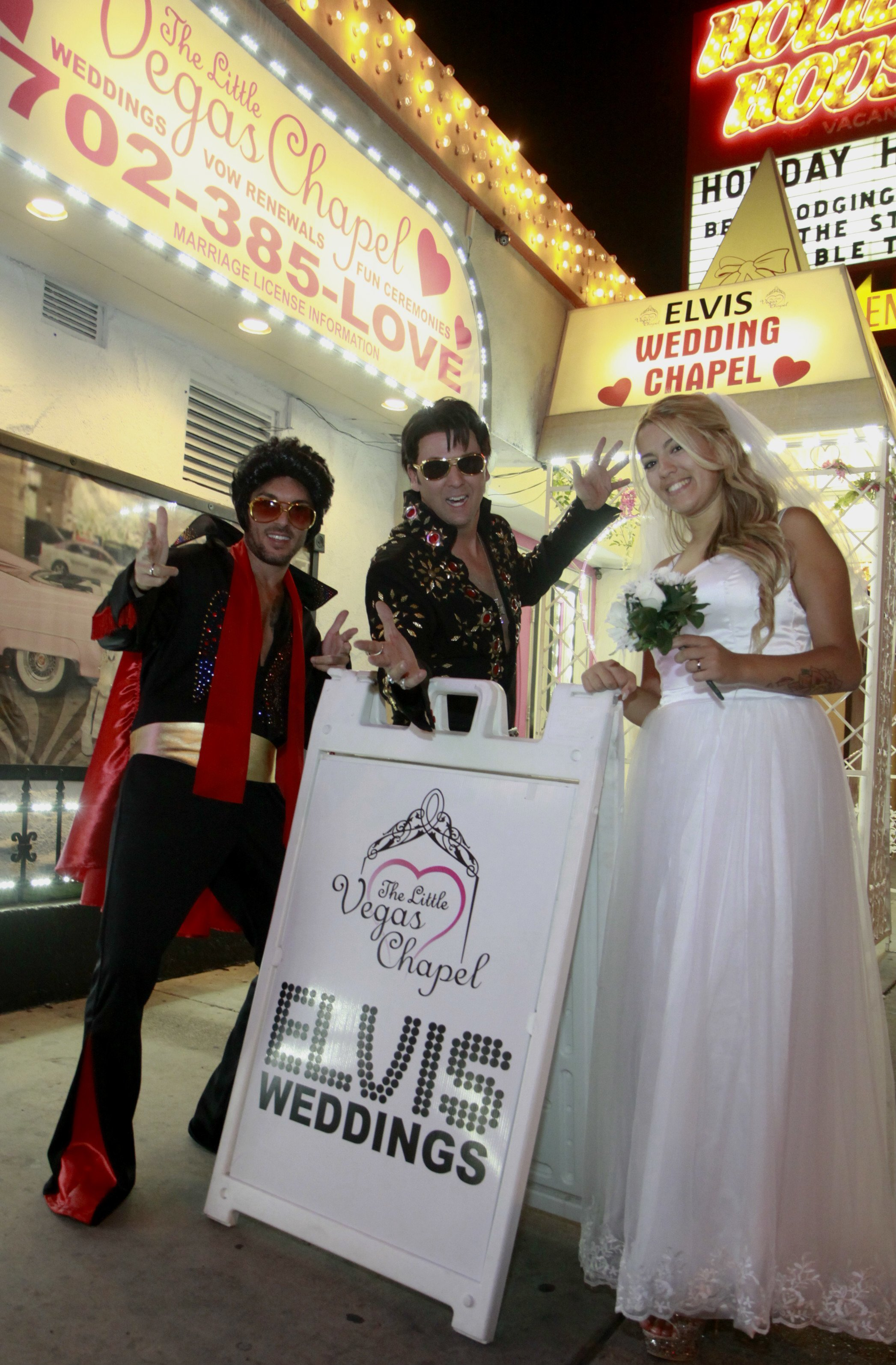 groom dressed as elvis, Elvis minister and Bride stand outside chapel next to Elvis weddings sign.