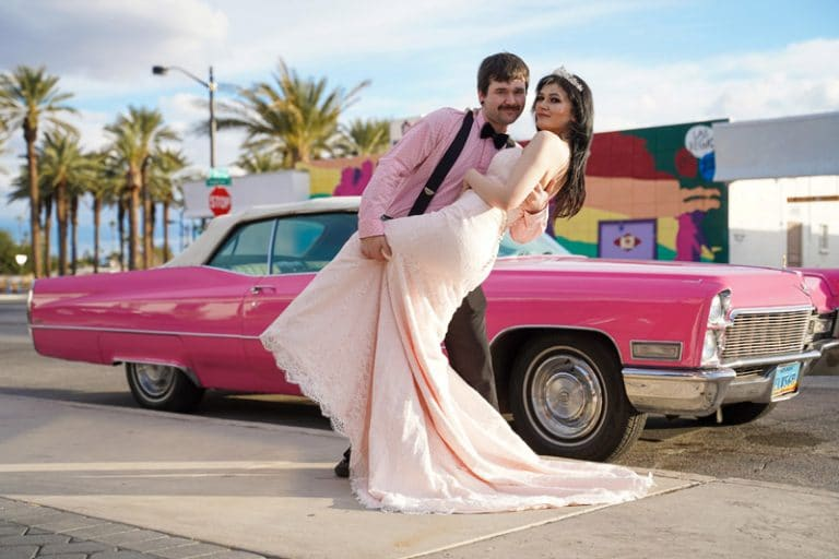 Groom dips bride in front of pink caddy