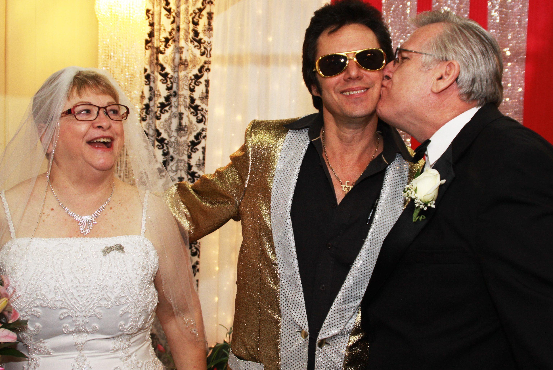 Groom kisses Elvis on the cheek, bride laughs