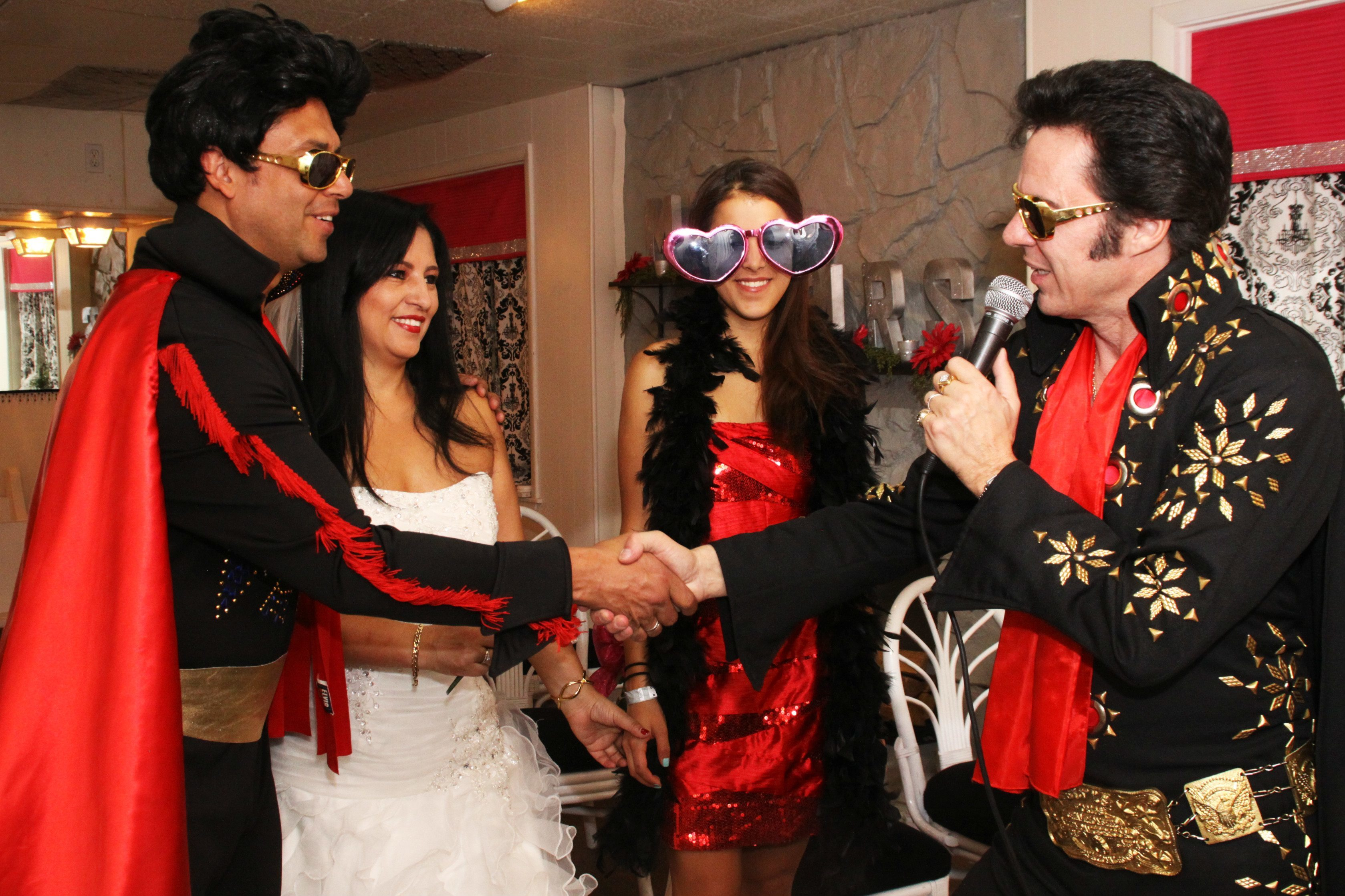 Elvis minister and Elvis groom shake hands with bride and bridesmaid in chapel.